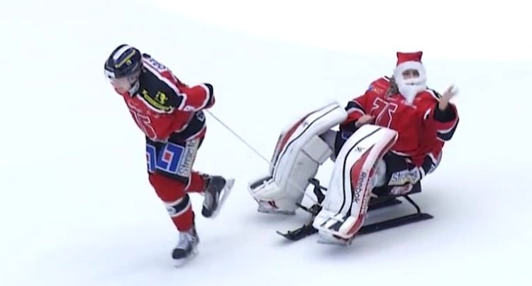 Julias Hudacek, pretending he's Santa Claus, being pulled across the ice on a sled by a teammate.